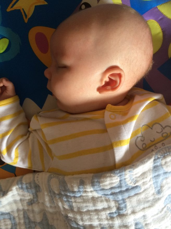 sleeping baby on play gym two months old