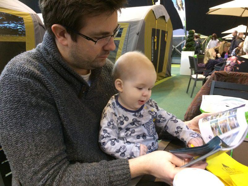 Baby looking at Brochure at Camping and Caravan Show