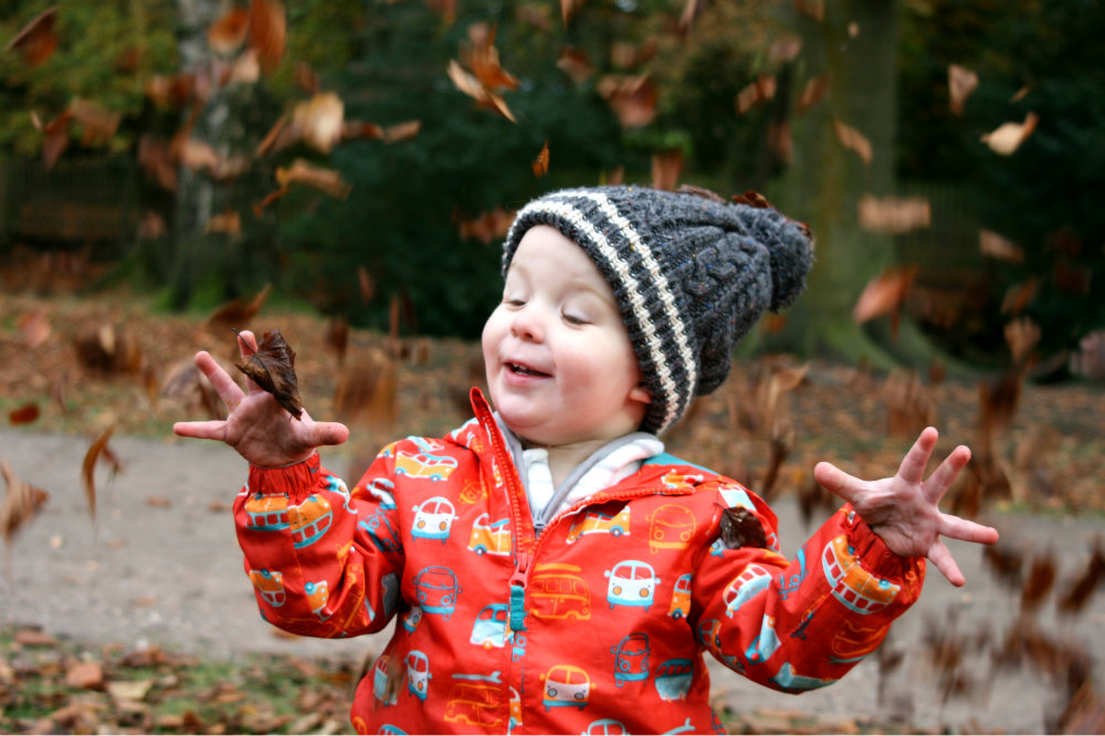 Happily playing in the leaves - a look of pure joy with eyes closed wearing a bobble hat