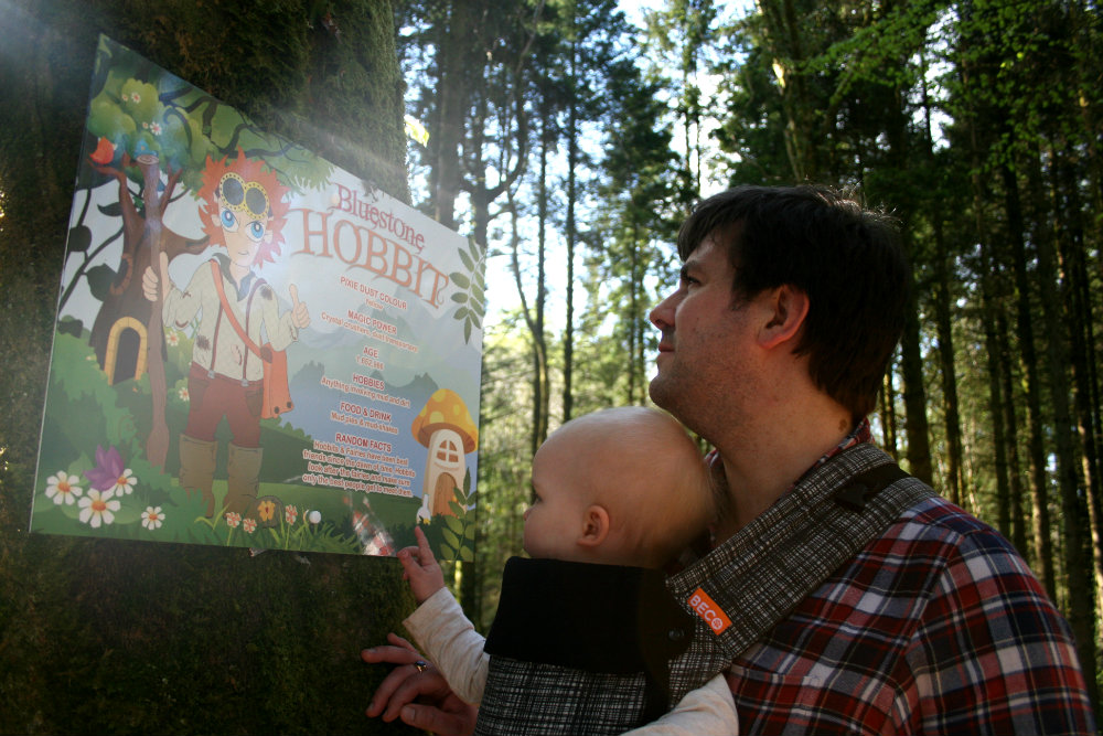 Daddy carrying baby in carrier on front, looking at a sign in the forest at Bluestone