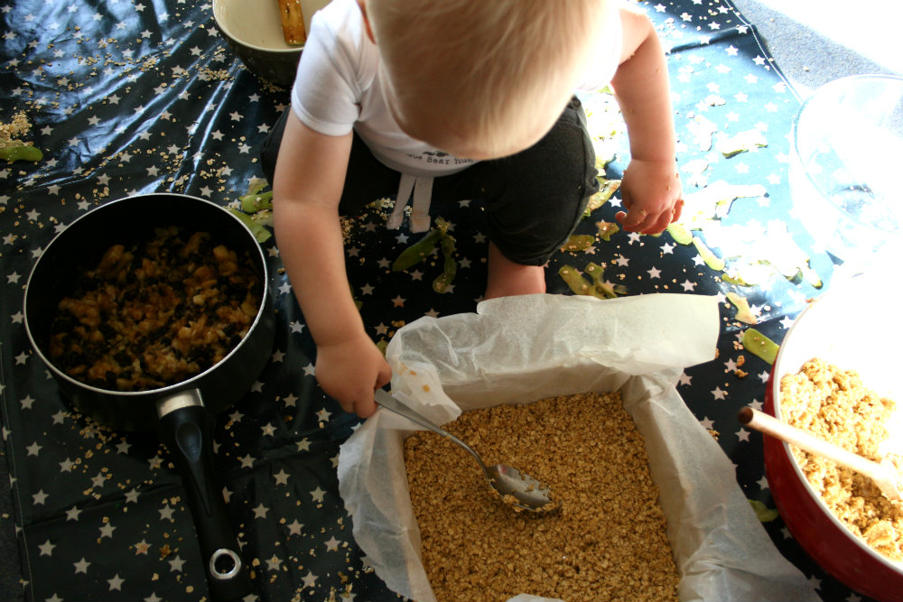Flapjack making with a Toddler, smoothing out the mixture