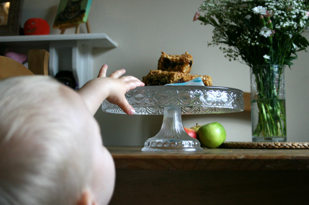 Little toddler hand reaching up to flapjacks on a cake stand