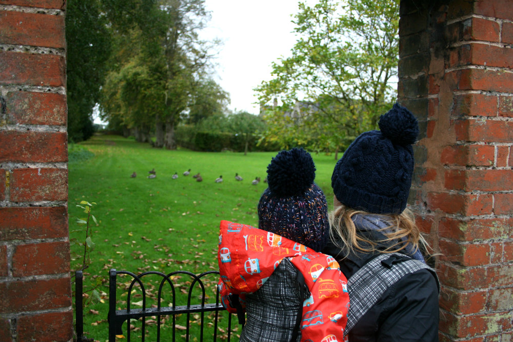 Pointing out the ducks at Coughton Court - photo of Pickle and Mommy from behind looking through an archway at some ducks
