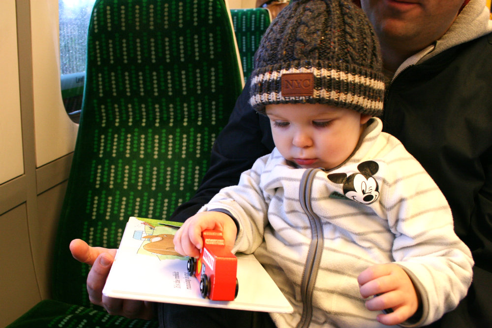 Pickle sat on a train reading a book and playing with a fire engine