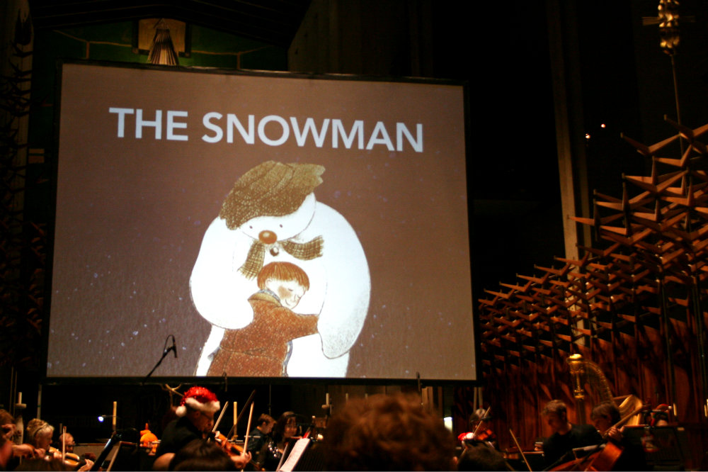 The Snowman animation screen projected above the orchestra in Coventry Cathedral