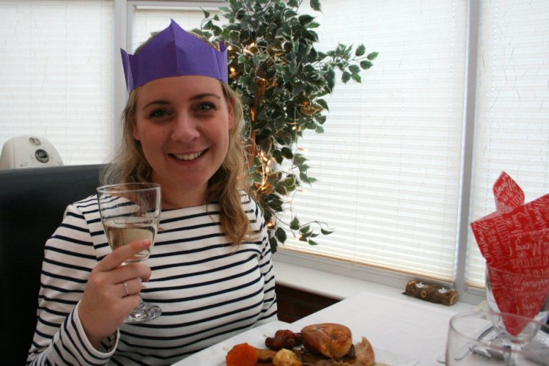 Holly wearing a Joules Harbour Top wearing a Christmas Paper Hat and holding a glass of wine