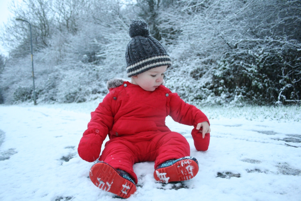 Toddler sat in the snow with a big red pram suit on
