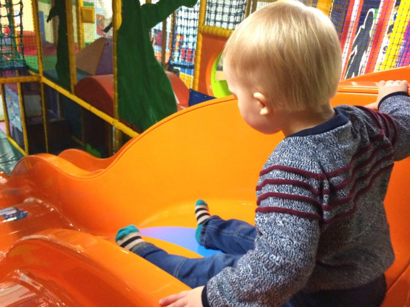 Sitting at the top of the slide at 360 Play Redditch