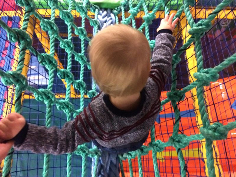 Toddler walking over a rope bridge brightly coloured at 360 Play Soft Play Centre