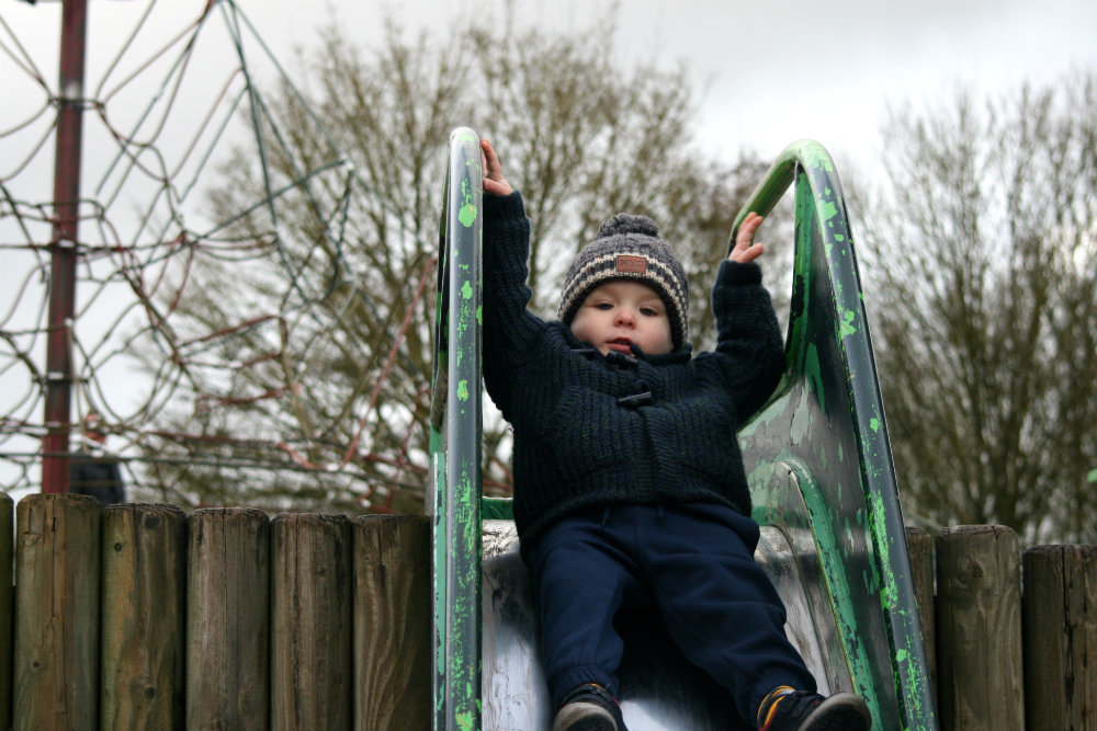 Sliding down the slide on his back wearing a bobble hat
