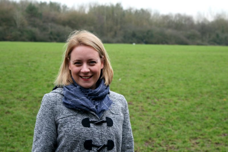 Holly stood in a field wearing a coat with new straightened hair