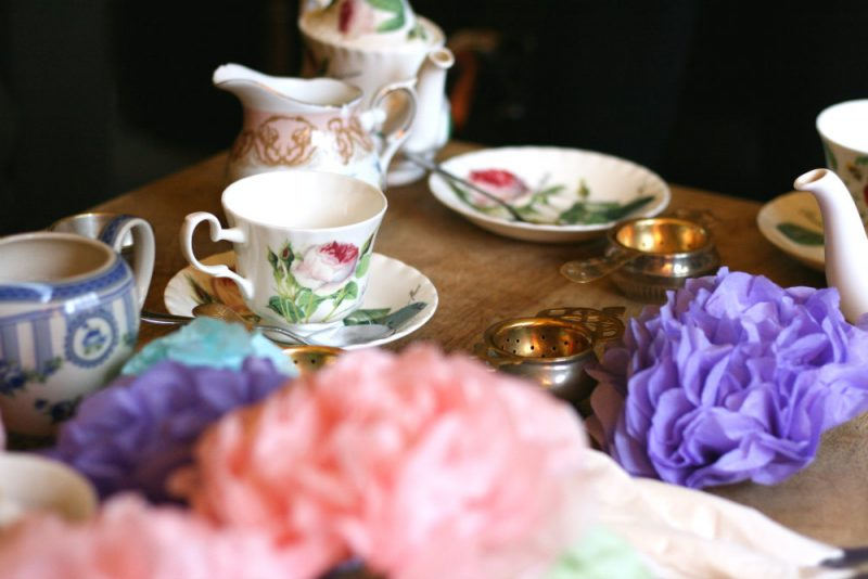 China tea set on coffee table with tissue paper pompoms