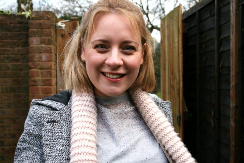 Grey jumper with pink sparkles with a coat and scarf outside