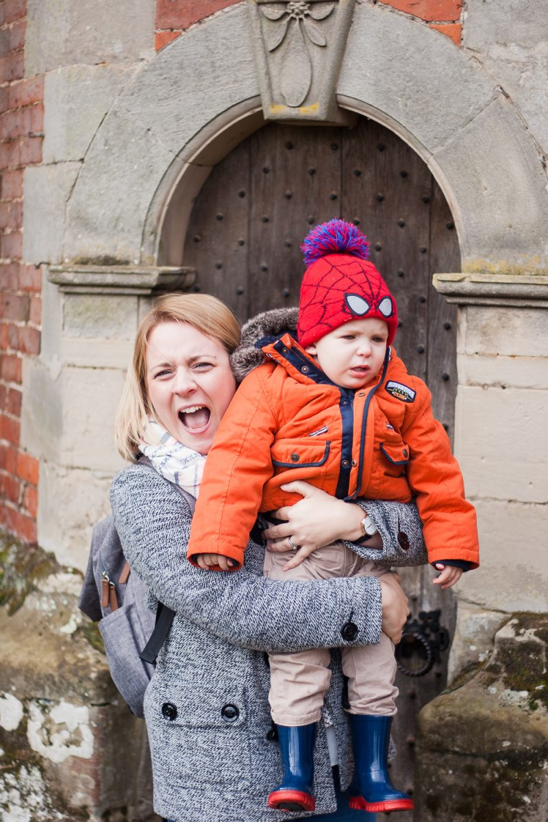 Pickle having a tantrum, being held by Mommy in front of a door at National Trust Charlecote Park
