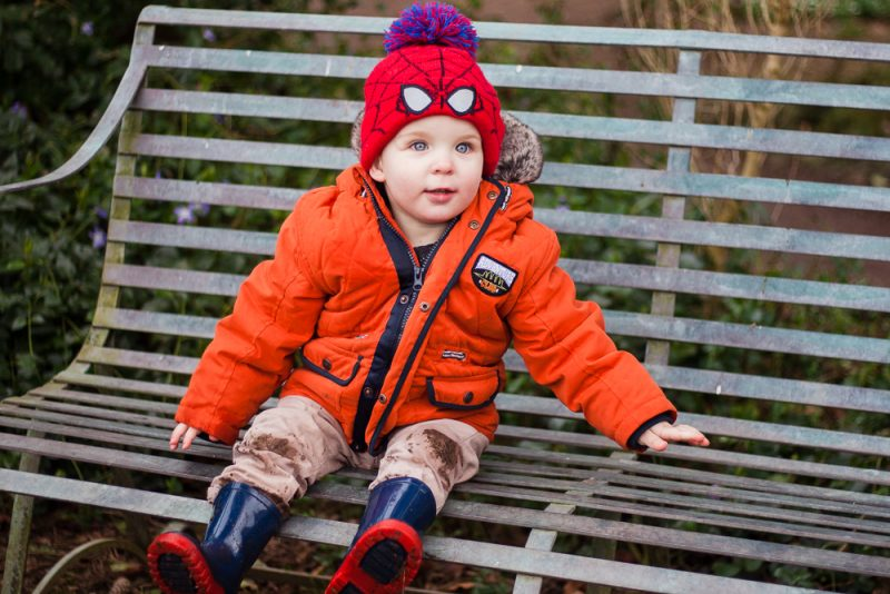Muddy trousers and knees, toddler sitting on a bench