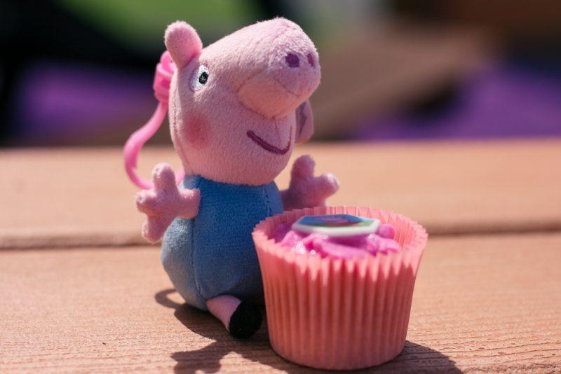 George Pig keychain teddy sitting behind a Peppa Pig cupcake