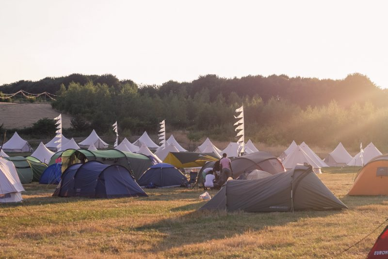 The camping field at Timber Festival with the glamping pods in the background
