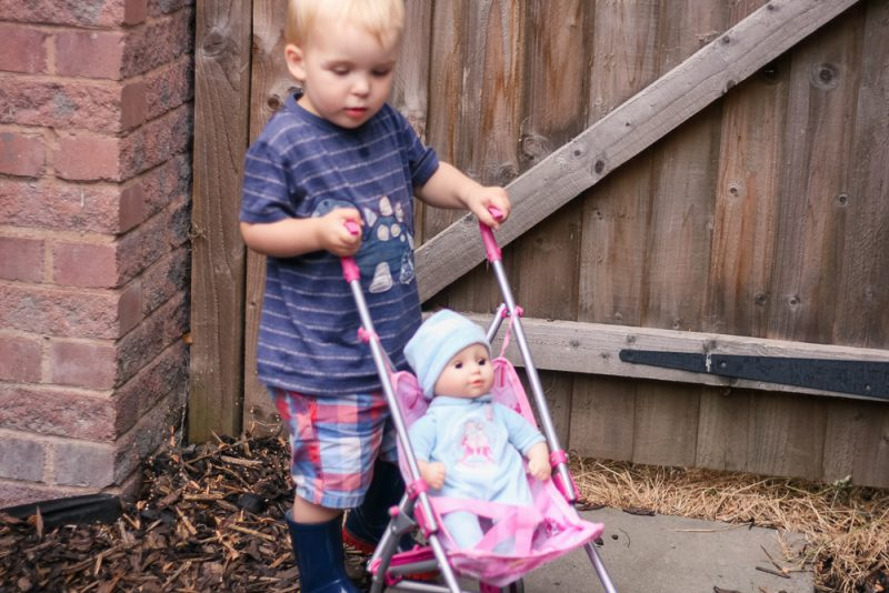 Pickle pushing his First Baby Annabell in a pushchair in the garden, in summer wearing his wellies