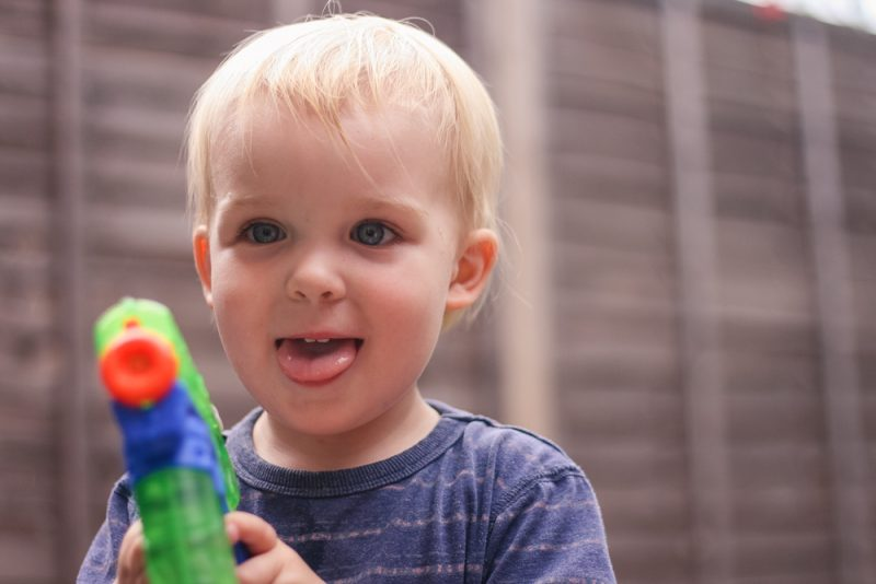 Cheeky boy with a water pistol playing outside