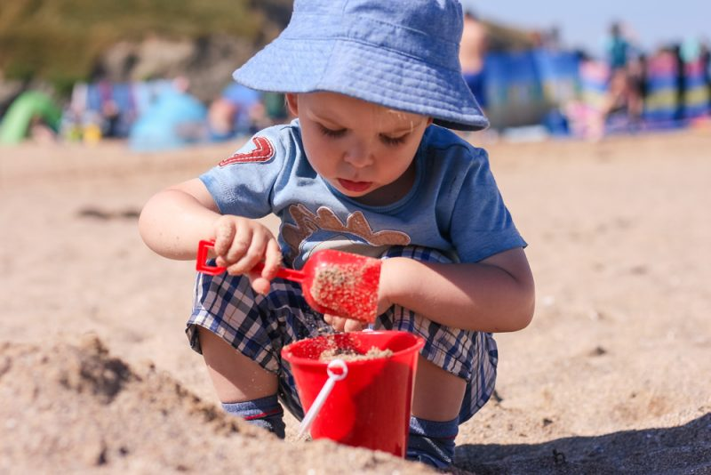 Concentrating on sandcastle building at Holywell Bay Beach