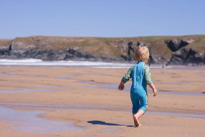 Pickle running along the beach in his Splash About UV Combi Suit