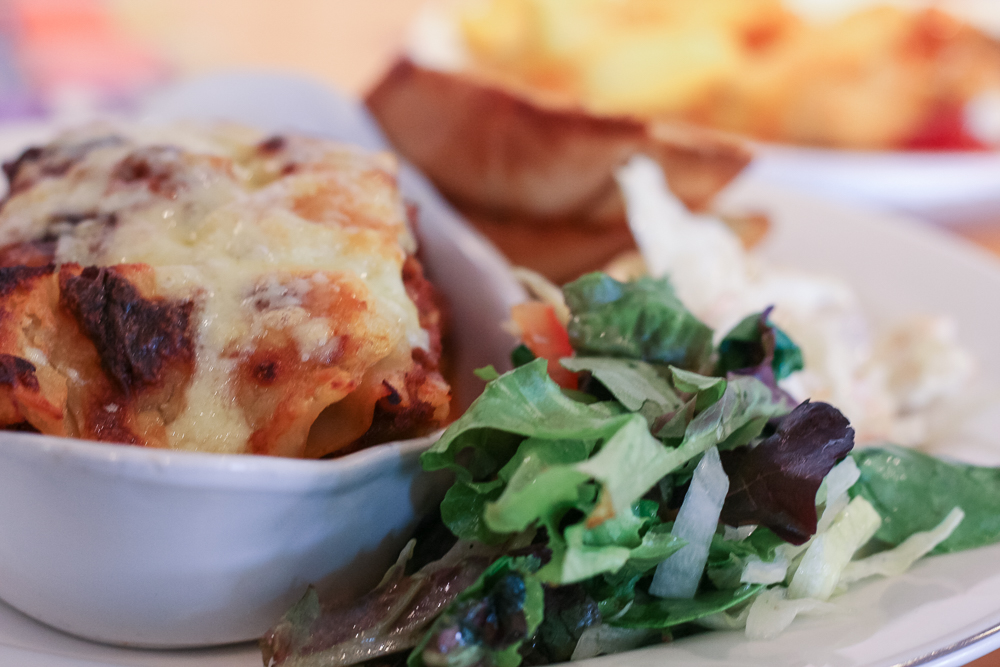Homemade lasagne with garlic bread and salad