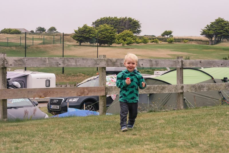 Pickle standing outside our tent with the terraces below overlooking the fishing ponds and golf course