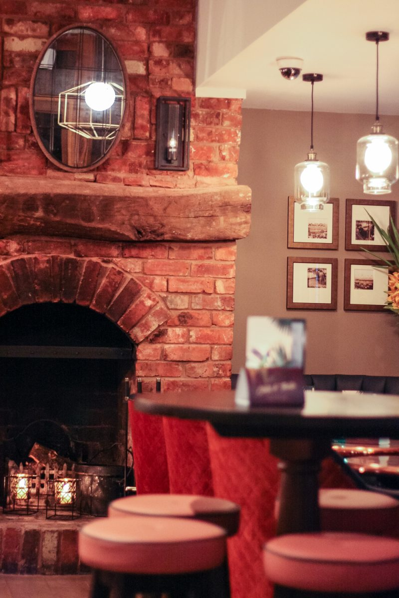The cosy fireplace at The Victoria Inn, well decorated with candles and pretty light shades