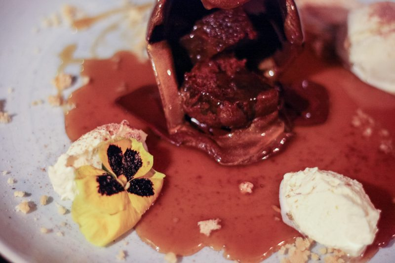 Melted chocolate bomb with gorgeous flowers and sticky toffee sauce