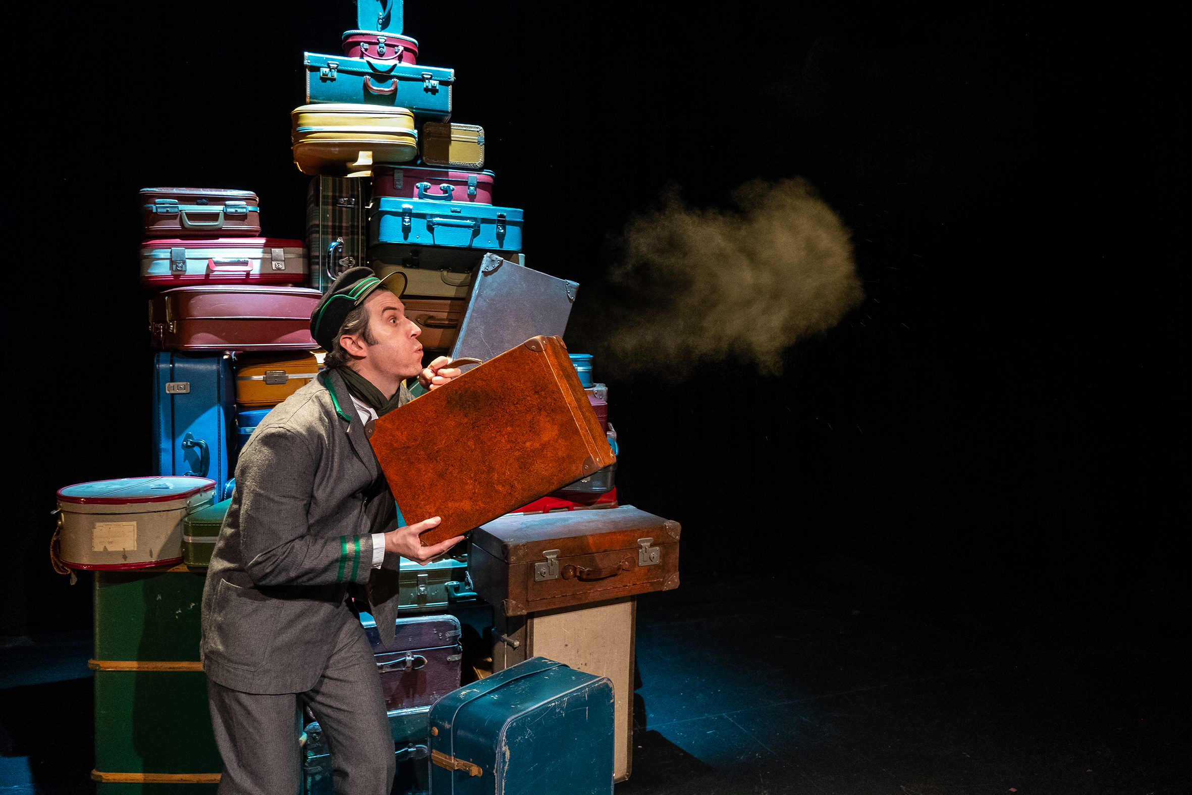Press Image from Little Gift Theatre show for children a man standing in front of lots of suitcases