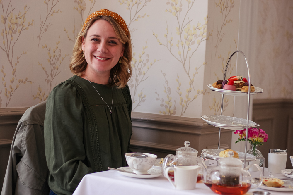 Smiling Holly wearing a headband at afternoon tea wearing Marks and Spencer top