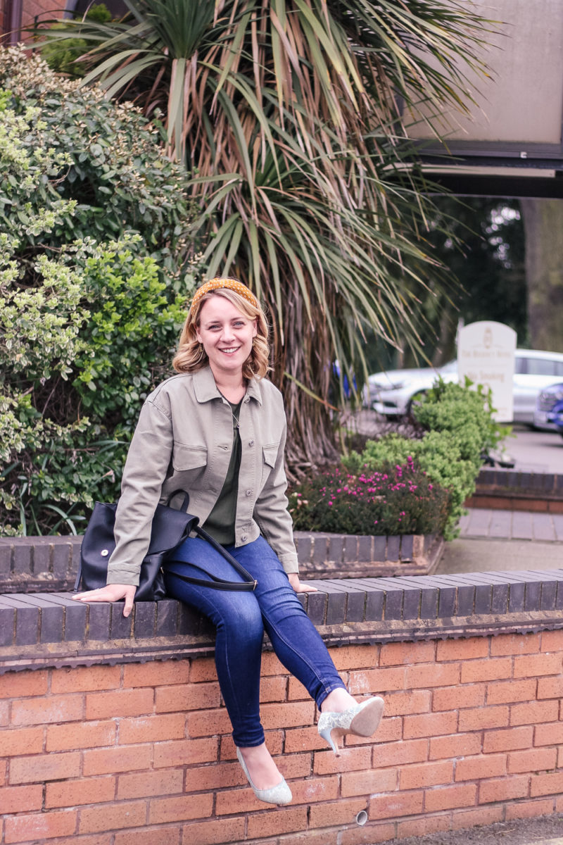 Sitting on a wall, wearing khaki cropped utility jacket, jeans and trainers