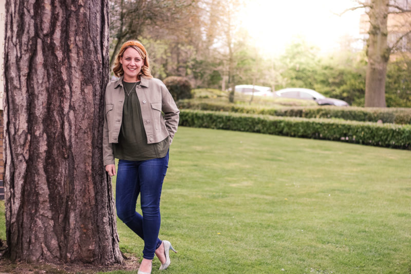 Posing against a tree wearing M&S clothing