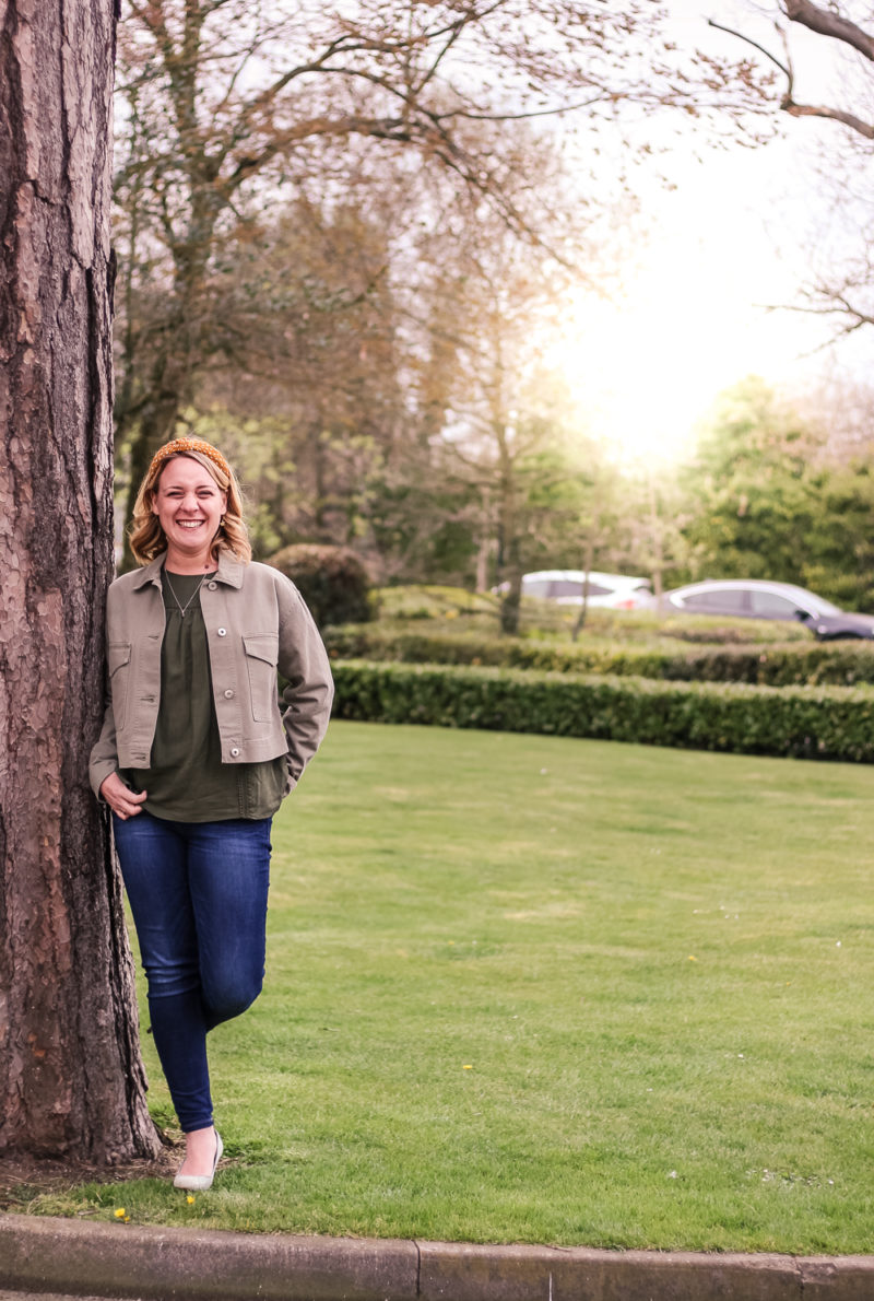 Laughing whilst leaning on a tree wearing Marks & Spencer clothing