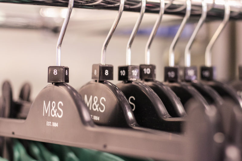 Close up of clothing hangers with size tags on