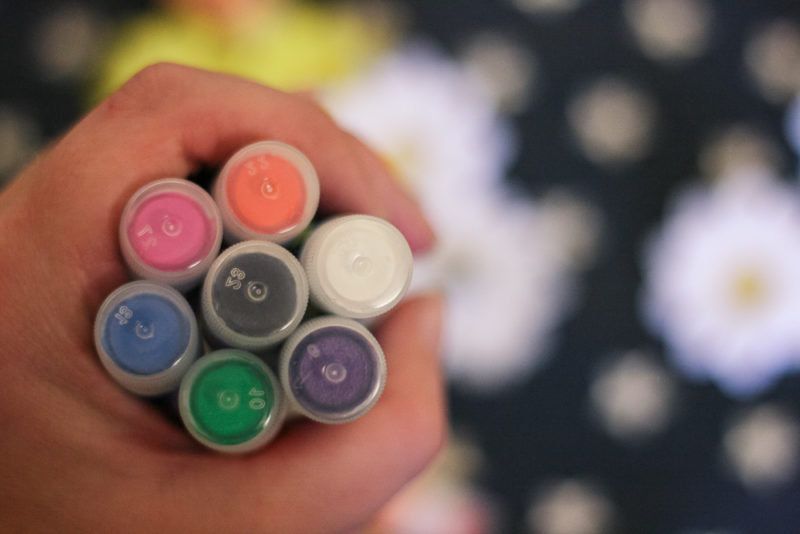 Holding a selection of paint sticks in hand showing the colours