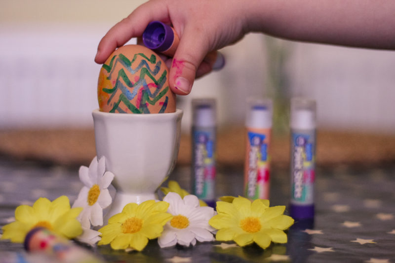 Easter Egg painted with Little Brain paint sticks in an egg cup with flowers