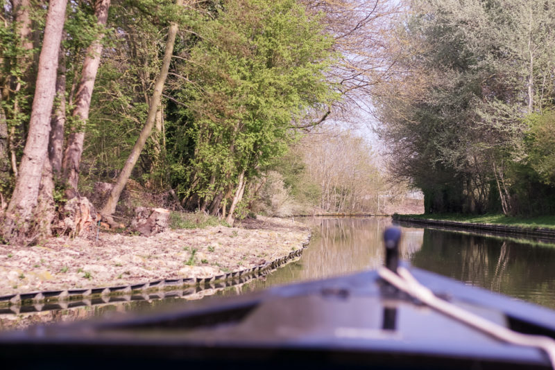 The front of the canal boat out of focus, looking at the route ahead.