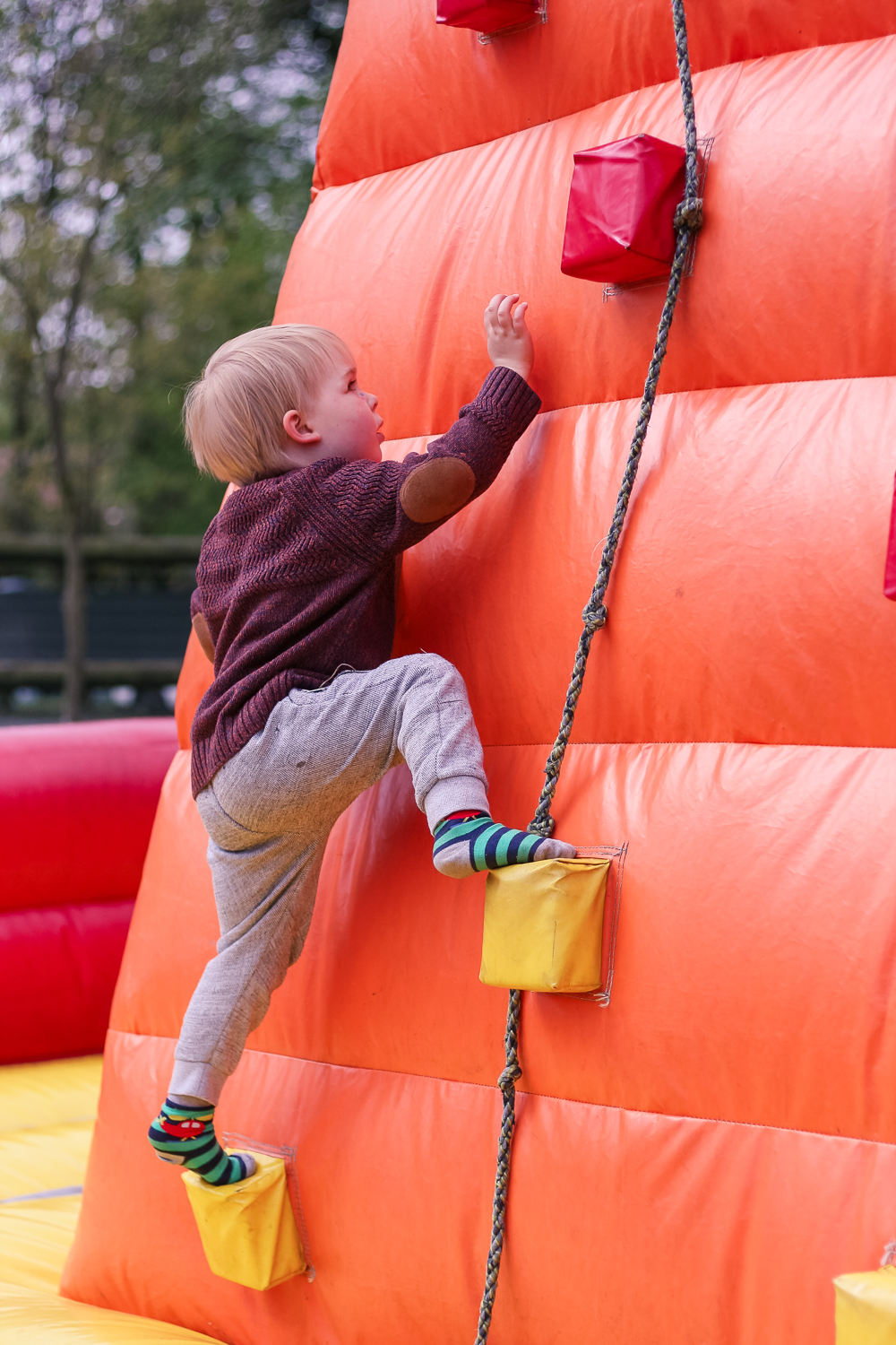 Climbing the inflatable climbing wall at Golden Valley Campsite