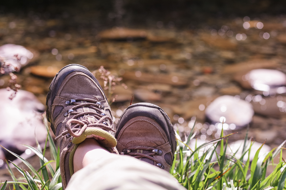 Legs crossed enjoying a walk by a river and waterfall