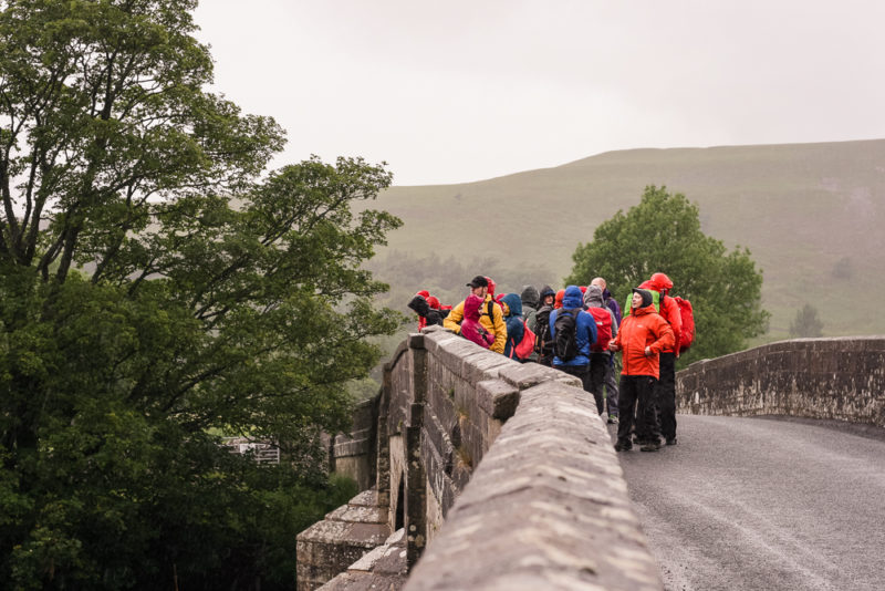 A group of walkers huddling in the rain