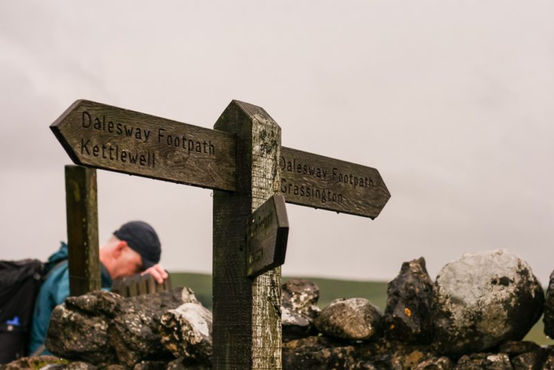 Signpost by a dry stone wall during a walk with Blacks and The North Face by Team Walking