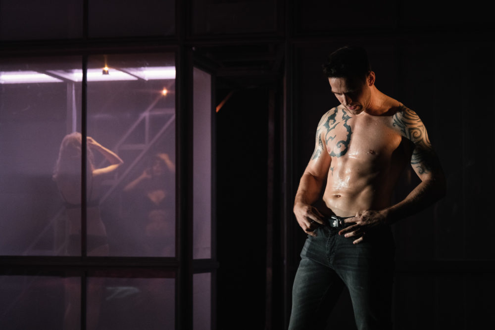 A shirtless man buckles up his jeans whilst a girl in underwear is in a bathroom behind him.