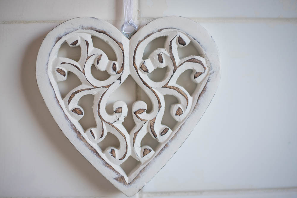 White wooden heart in front of white whiles