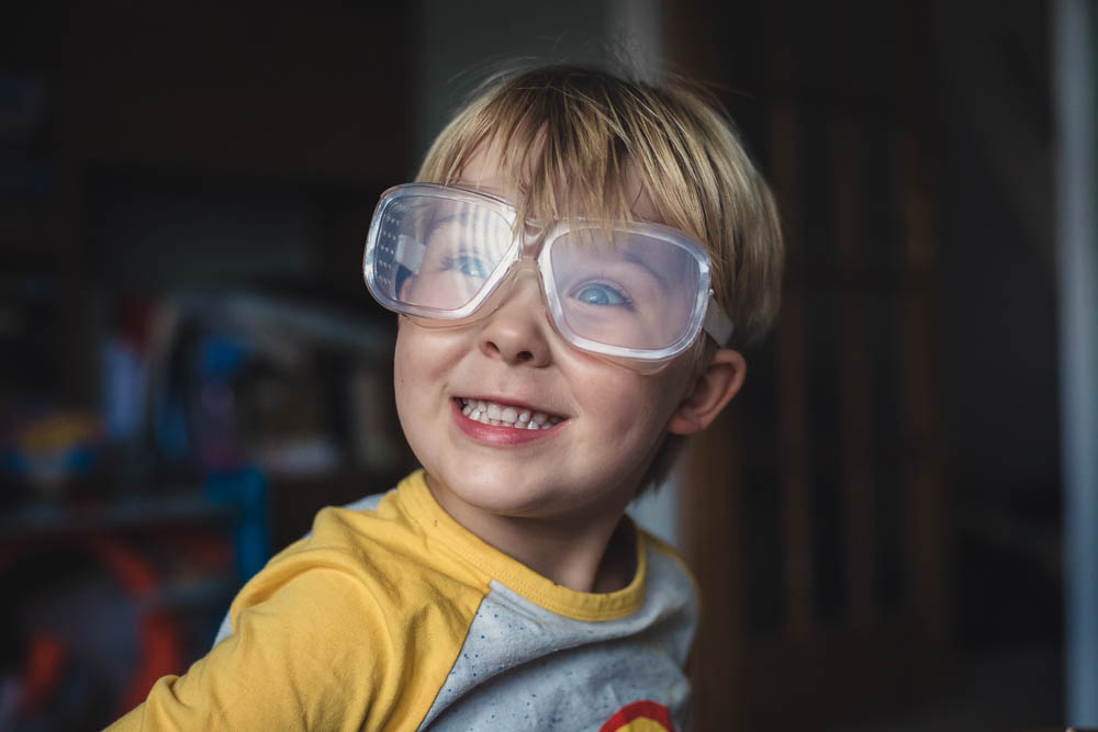 Happy four year old wearing scientist goggles with a big grin