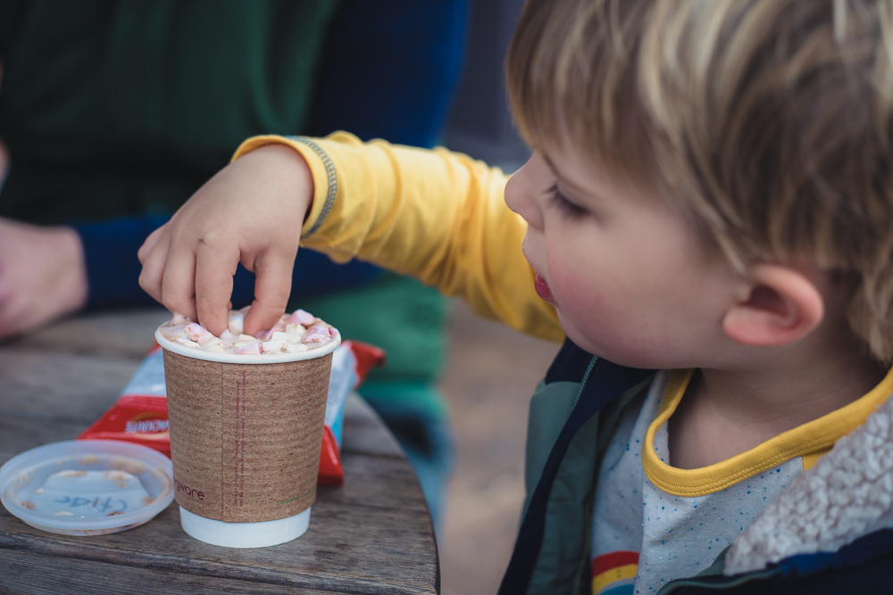 Child dunking crisps into a takeaway hot chocolate cup