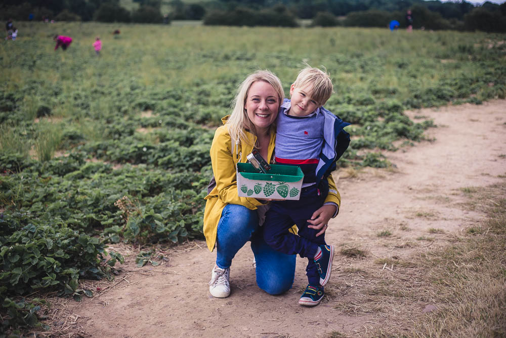 Holly and Pickle holding a punnet of strawberries at the Scaddows Farm Strawberry field PYO fruit