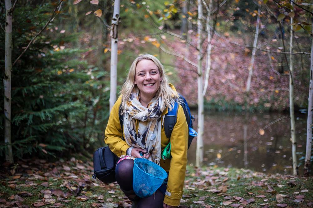 Holly kneeling on the floor holding a net of leaves at Bodenham Arboretum