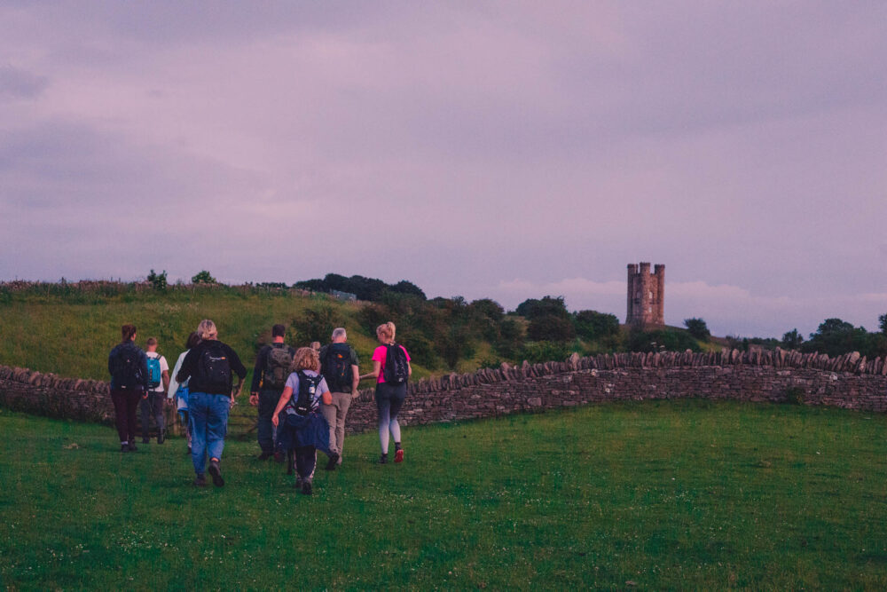 A group of hikers at sunset at Broadway Tower, organised through MeetUp