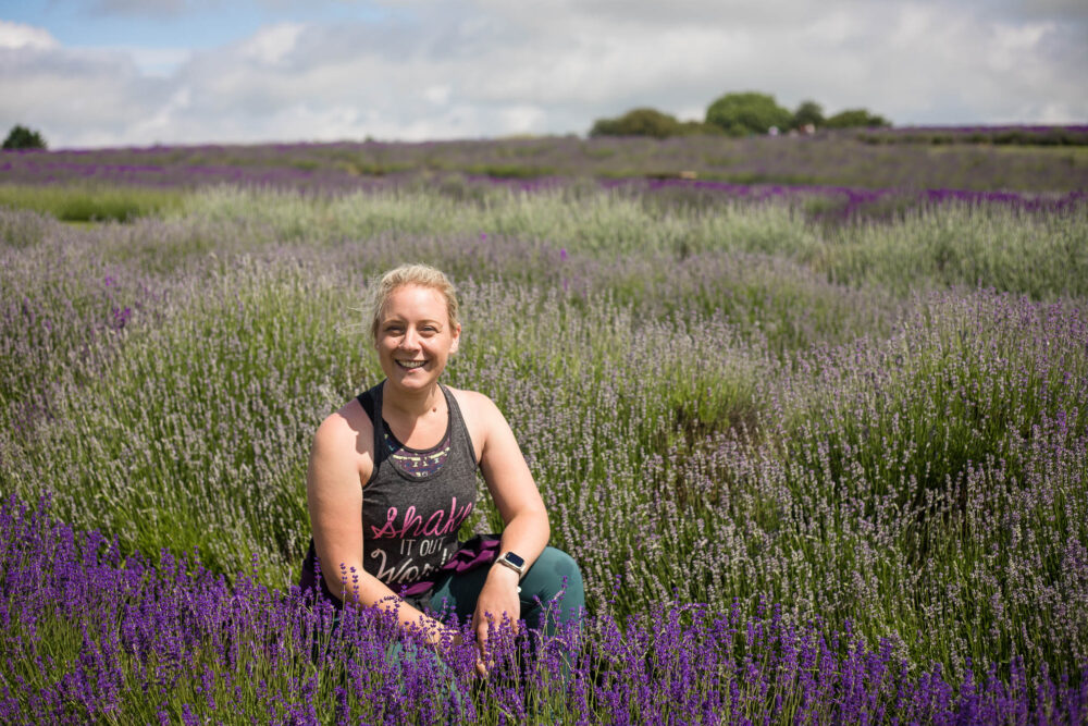 Holly crouching in lavender at Cotswold Lavender walk during an organised hike with Walking The Hills